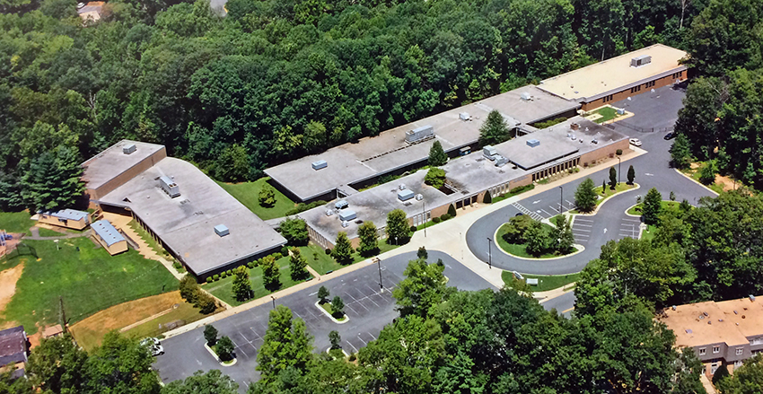 Color aerial photograph taken from a helicopter above North Shore Drive looking toward our building at an angle from due south. Compared with the earlier aerial photograph from the 1960s, you can see there have been three additions to the building: the gymnasium, and two classroom wings that have connected the formerly separate houses.
