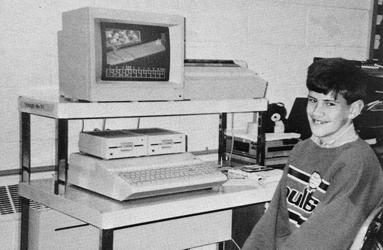 Black and white photograph of a student sitting in front of a computer workstation in 1990. The apple computer has a large keyboard built into the hardware assembly, a small CRT monitor, two large floppy disk drives, and a dot matrix printer.