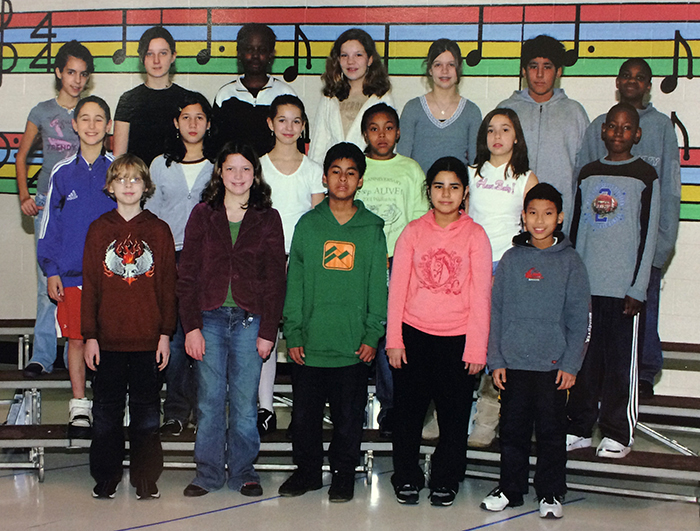 Yearbook photograph of the Lake Anne Ringers from 2005 to 2006. 18 children are pictured, standing in rows on three risers. Music notes are painted on the classroom wall behind them in colorful shades of red, blue, yellow, and green.
