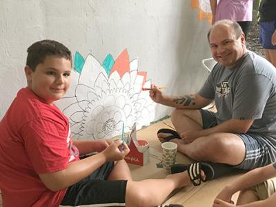 A student and his dad enjoy working on the mural.